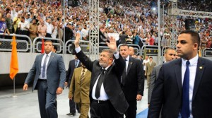 Egyptian President Mohammed Morsi waves as he arrives at a rally called for by hardline Islamists loyal to the Egyptian president to show solidarity with the opposition in Syria, in a stadium in Cairo, Egypt, Sunday, June 15, 2013. (AP / Egyptian Presidency)