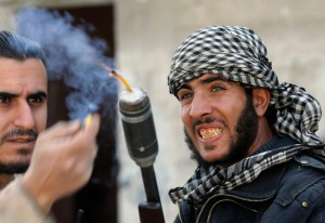 ighters from the Free Syrian Army's Tahrir al Sham brigade light the fuse of an improvised grenade, ready to launch it from a modified shotgun, toward Syrian Army soldiers in the Arabeen neighborhood of Damascus, on February 9, 2013. (Reuters/Goran Tomasevic)