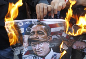 A protester holds a poster burning on which is depicted former US president George W. Bush taking off a mask of current President Barack Obama during a demonstration of supporters of Syrian regime near the US embassy, east of Beirut against a possible US military strike on Syria on September 7, 2013. (AFP Photo)