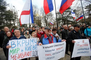 Pro-Russia demonstrators hold Russian and Crimean flags and posters as they rally in front of the local parliament building in Crimea's capital Simferopol, Ukraine, Thursday, March 6, 2014.