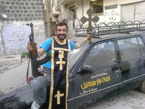 A rebel in the old city of Homs, where 80,000 Christians were forced out. He poses with a machine gun in one hand and a processional cross in the other; he is wearing part of the funeral vestments of a Syriac Orthodox priest. In this image he is seen leaning against the funeral hearse of St. Joseph's Syriac Orthodox Parish. It is said that the rebels in the area used the hearse to transport weapons around the district.