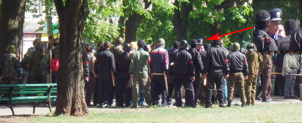 A group of men with red bands receive instructions from a person in police uniform, Odessa, May 2, 2014.