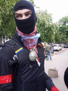 Strange combination of contradicting identifications (St.George ribbon and Ukrainian flag) on the bulletproof vest of a fighter on the street of Odessa. Take note of the red band.