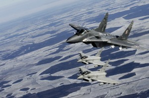 A Polish Air Force MIG-29 fighter (top) and Italian Air Force Eurofighter Typhoon fighters participate during a NATO air policing mission patrol over the Baltics from the Zokniai air base near Siauliai February 10, 2015. REUTERS/Ints Kalnins