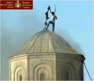 "An Albanian ""rebel"" fights the cross on the top of the Serbian church in Podujevo."