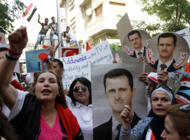 Syrian citizens hold portraits of President Bashar al-Assad as they protest against sanctions outside the EU offices in Damascus, Sept 2011.