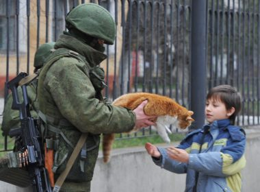 Russian soldier hands a cat to a boy in Crimea, February 2014.