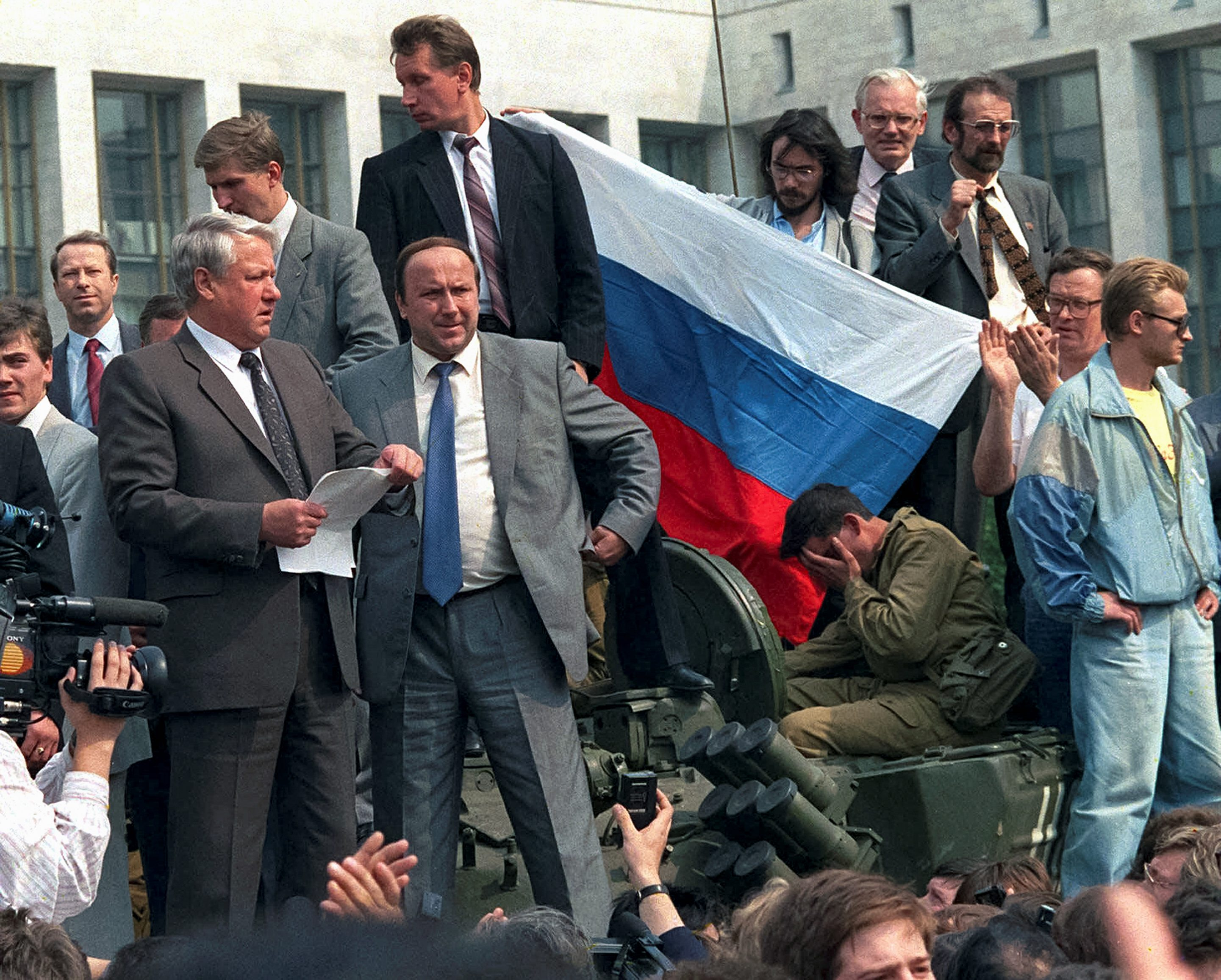 Russian President Boris Yeltsin, foreground left, addresses the crowd standing atop of a tank in front of the Russian Government building, also known as White House