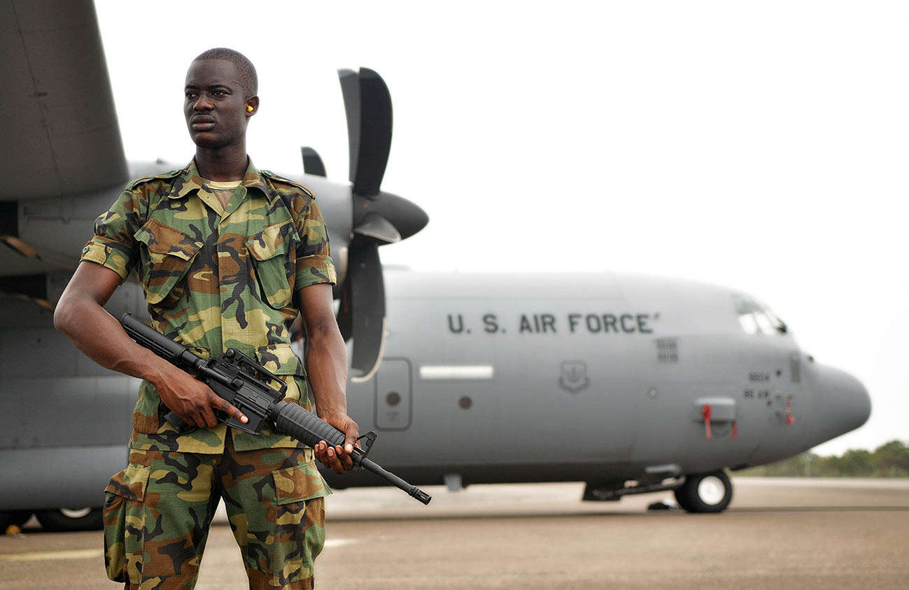 A member of the Ghanaian air force guards a U.S. Air Force C-130J Hercules
