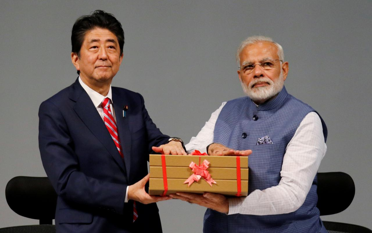 Japanese Prime Minister Shinzo Abe (L) and his Indian counterpart Narendra Modi hold a replica of a brick during the India-Japan Annual Summit, in Gandhinagar, India, September 14, 2017