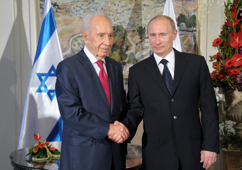 Israeli President Shimon Peres shakes hands with Russian President Vladimir Putin