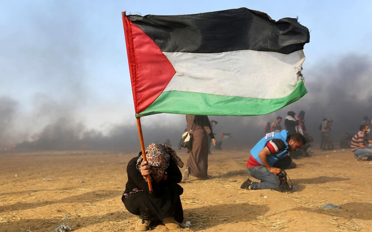 A Palestinian protester takes cover after Israeli forces attacked protesters