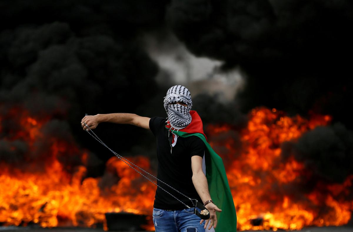 Palestinian demonstrator holds a sling