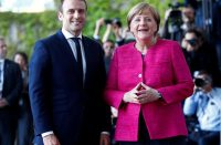 German Chancellor Angela Merkel and French President Emmanuel Macron arrive at a ceremony at the Chancellery in Berlin