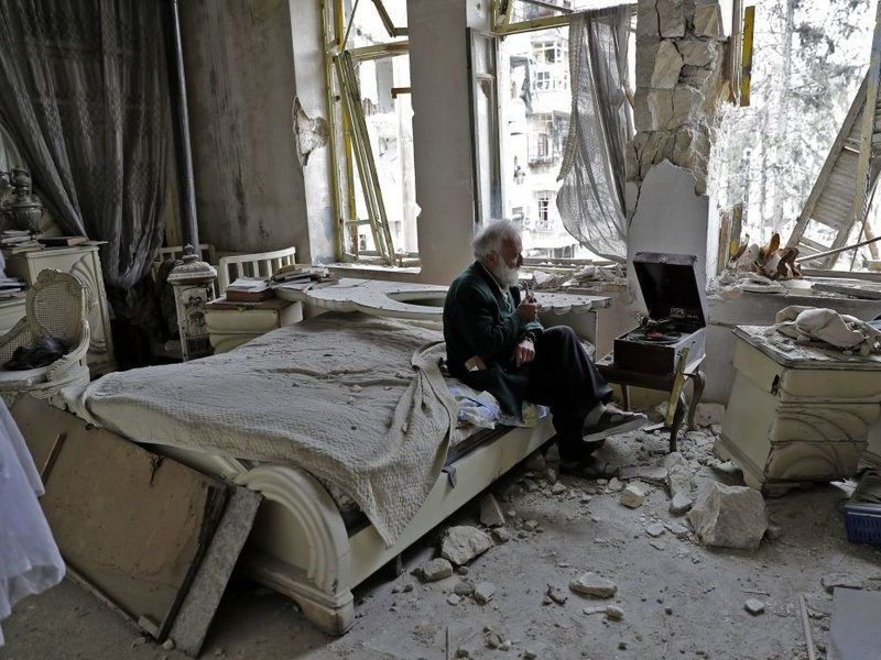 Abu Omar, 70, smokes his pipe as he sits in his destroyed bedroom listening to music on his gramophone in the neighbourhood of al-Shaar in Aleppo, Syria