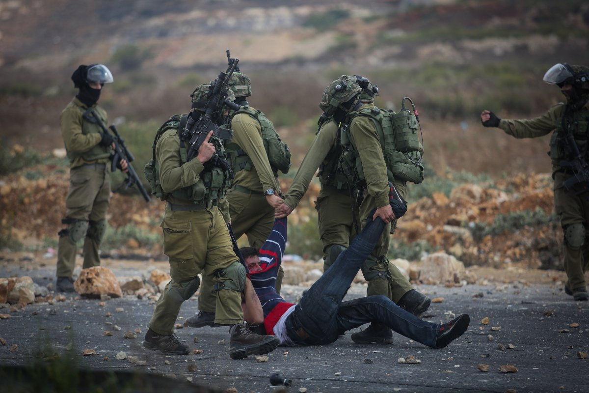 Israeli soldiers detain a Palestinian during clashes in Beit El, on the outskirts of the West Bank city of Ramallah, 2015