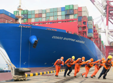 Workers wearing face masks rope a container ship at a port in Qingdao