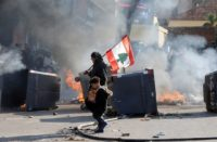 A protestor holding the Lebanese flag walks near burning barricades during a protest over economic hardship and lack of a new government in Beirut
