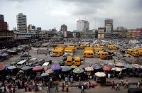 People walk past roadside stalls with umbrellas in the central business district, near Marina in Lagos