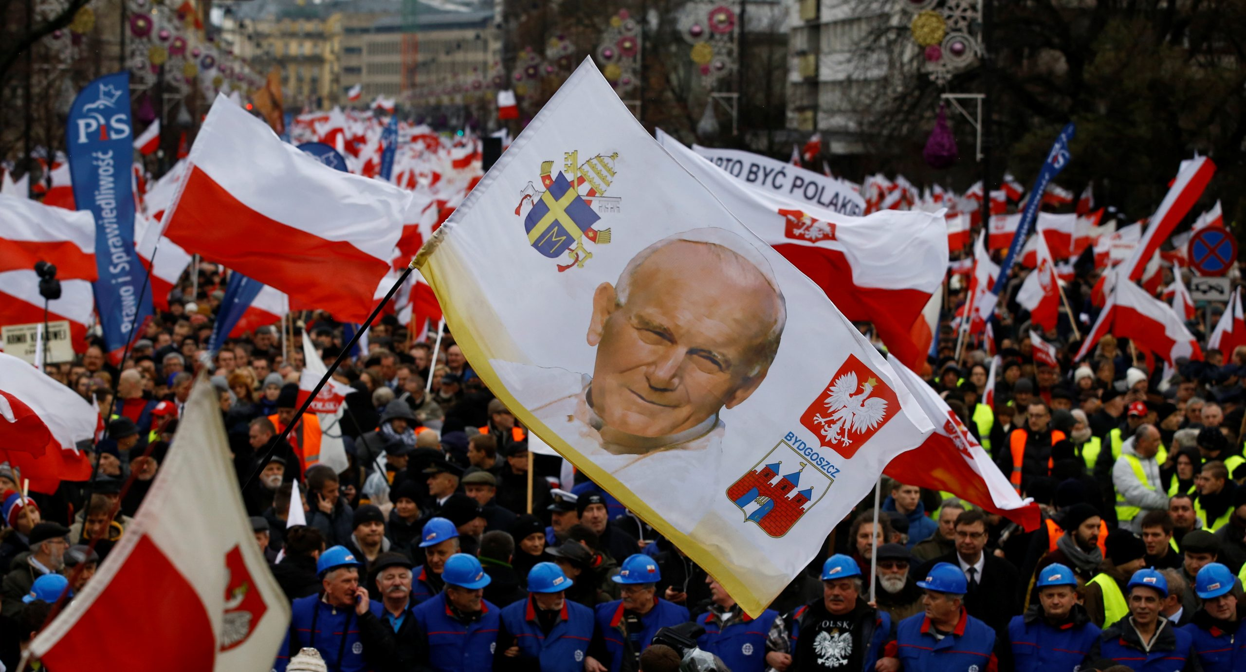 Supporters of Law and Justice party walk with a portrait of late Pope John Paul II during a pro-government demonstration in Warsaw